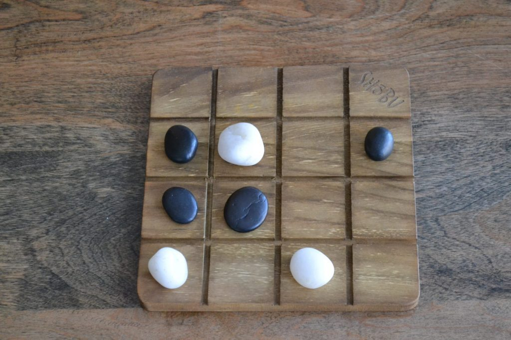 A single SHOBU board, showing a series of stones from both players -- none of which are safe from enemy attack.